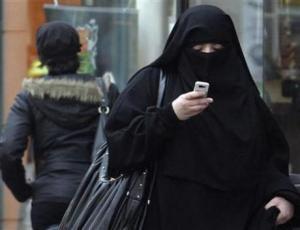 Mujer usando burqa camina por una calle en Saint-Denis, Francia.